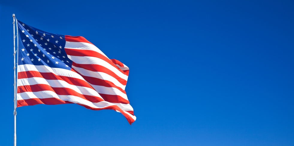 American flag fluttering in the blue sky
